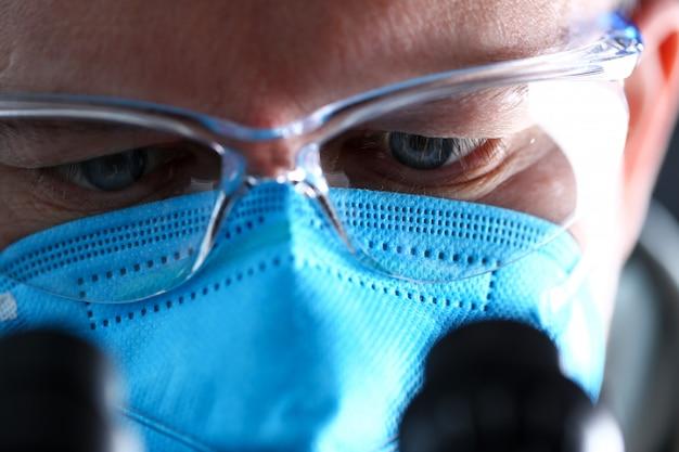 Мужской лабораторный работник смотрит на микроскоп в защитной маске