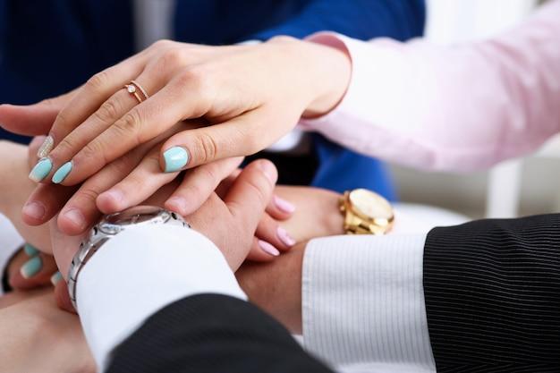 Группа людей в костюмах скрещенные руки в кучу