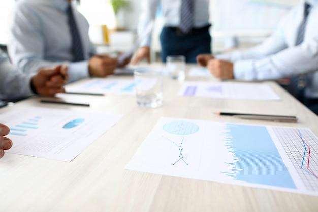 Бизнес диаграммы лежат на столе против группы людей