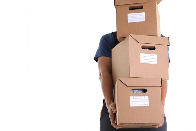 Специалист курьерской службы доставки несет коробки с