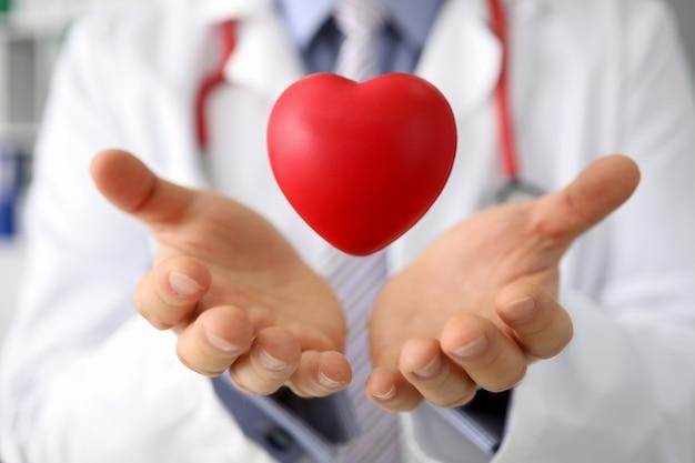 医者は病院に対して赤いグッズハートを手に保持します。
