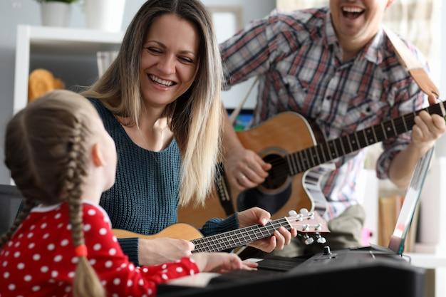 Счастливая семья играет на музыкальных инструментах