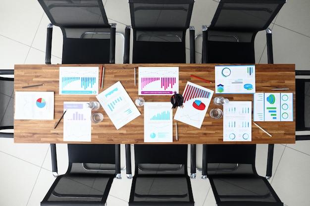 木製のオフィスのテーブルの上のビジネスグラフと紙