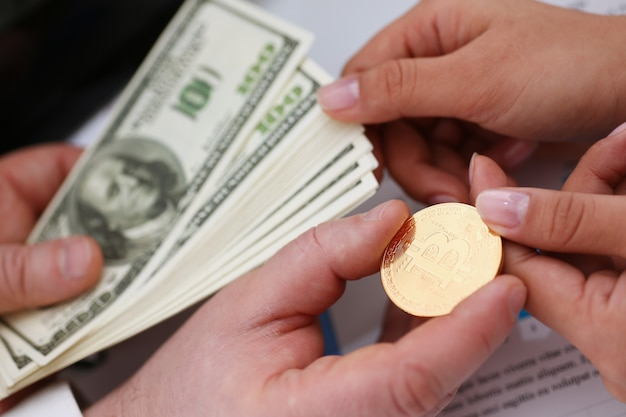 Руки с монеткой биткойн и веером долларов