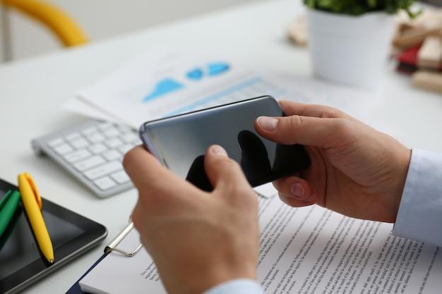 ビジネスマンは彼の手で新しいスマートフォンを保持