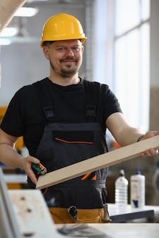 木の板を保持している笑顔の大工の肖像画