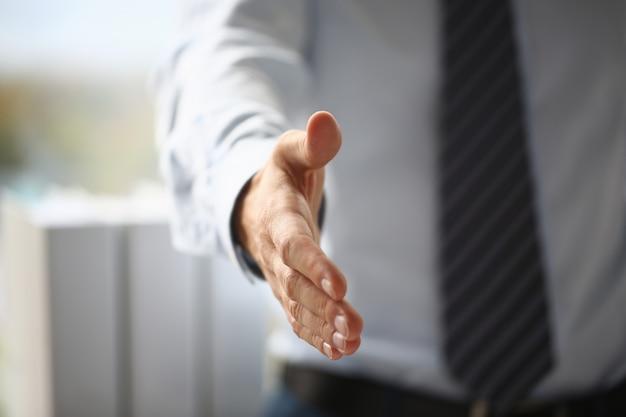 スーツとネクタイの男は、オフィスのクローズアップでこんにちはとして手を与える