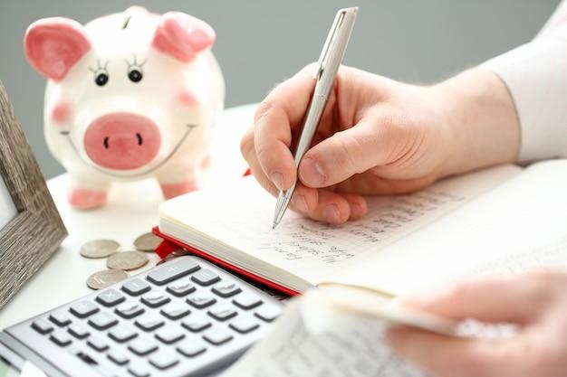Мужская рука делает некоторые заметки с серебряной ручкой на бумаге о денежном потоке