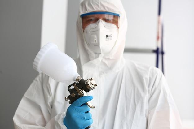 Рабочий держит в руках пистолет-распылитель в защитном костюме