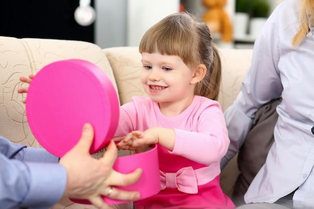 幸せな少女は彼女の両親からプレゼントボックスを開く