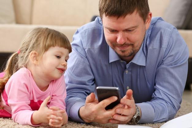 父と娘は携帯電話を使用して床に横たわる