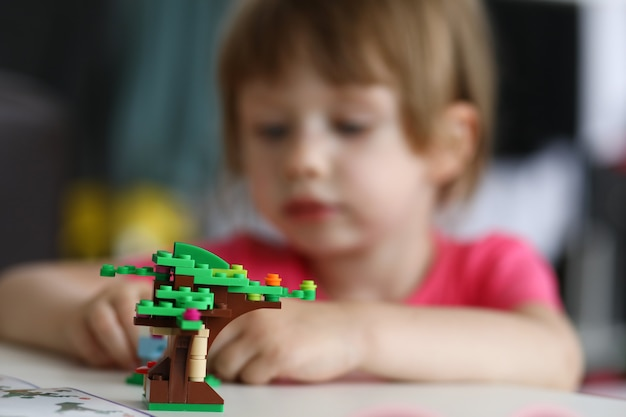 Маленький ребенок играет в конструктора и