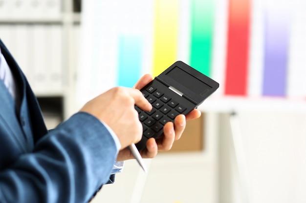 Мужская рука в костюме держит калькулятор нажатием кнопки