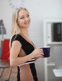 コーヒーの手でマグカップを保持している金髪の女性