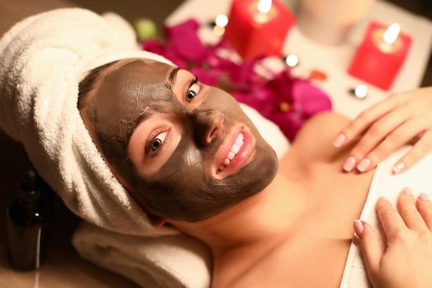 美女がスパサロンでチョコレートマスクを適用