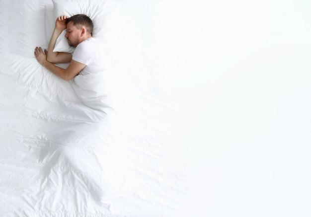 白いベッドで寝ている若い白人の美しさの女性