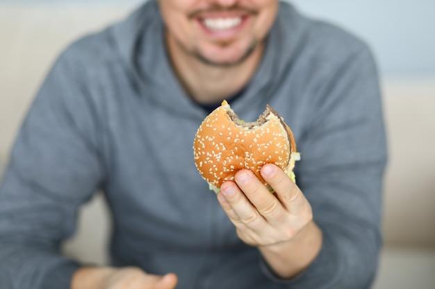 新鮮なハンバーガーを手に保持笑みを浮かべて男