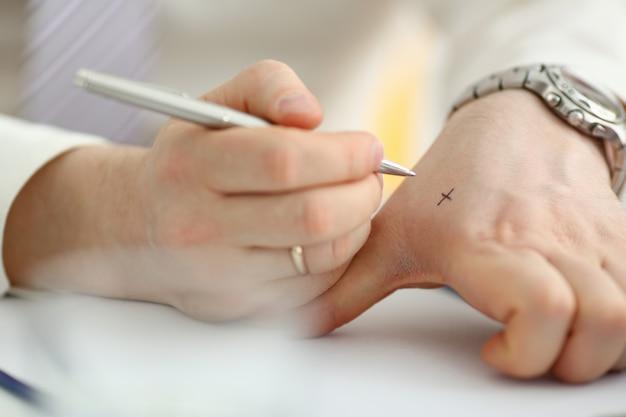 Самец делает крестик с серебряной ручкой на руке
