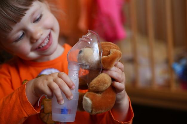 Счастливый ребенок делает ингаляцию дома
