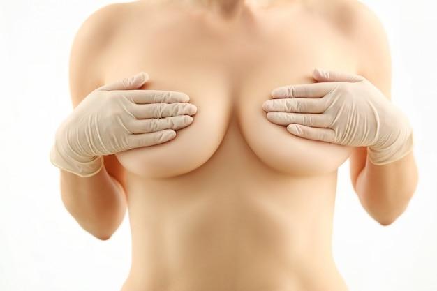 トップレスの女性が裸の胸の肖像画を保持します。