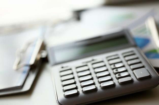 Лежит серебряный калькулятор с серой клавиатурой