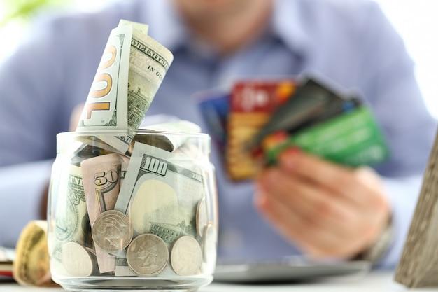 お金でいっぱいの大きな瓶がクレジットカードの束を持っている男性の手で作業テーブルに立つ