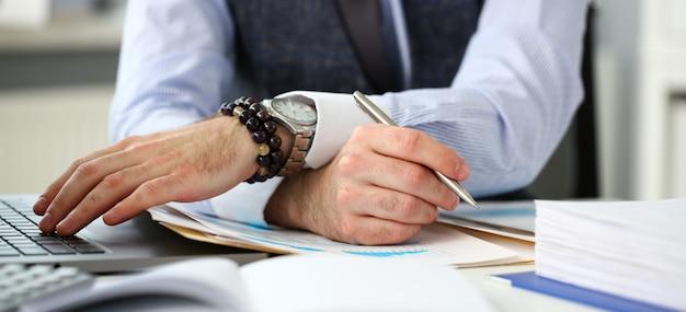 Клерк человек на рабочем месте в офисе с серебряной ручкой