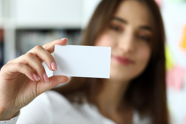 Женская рука в костюме дает визитную карточку посетителю