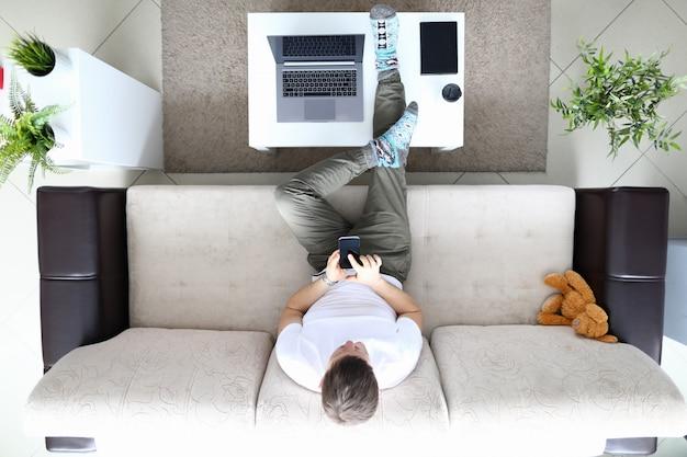 男はソファに座って、現代のスマートフォンを手に保持します。モバイルアプリケーションの概念を使用します。ソーシャルメディア中毒