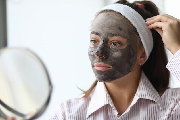 女性は、ホームスパチョコレートマスクの肖像画を作ります。