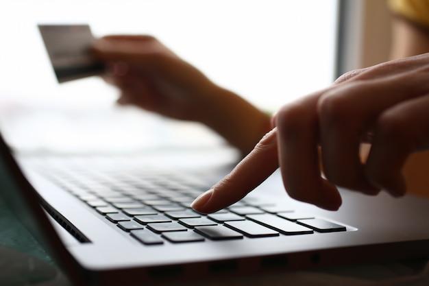男性の腕は、クレジットカードの押しボタンを保持します。