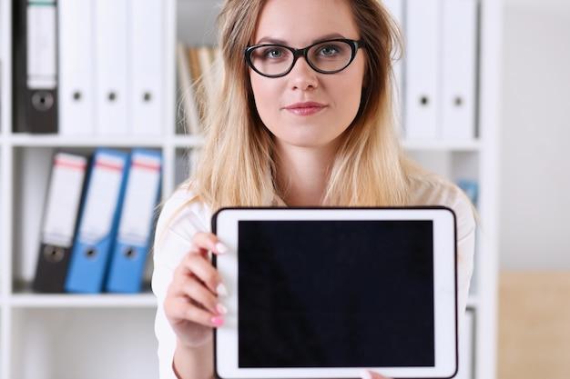 笑顔でカメラの先生を見てテーブルに座ってタブレットを手に保持しているオフィスでメガネの肖像画を着て美しい実業家は、テストペーパーをチェック成功を表現します。
