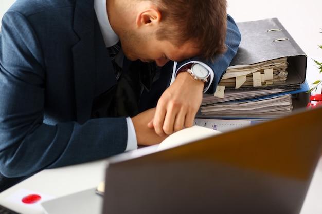 スーツの疲れたオフィスの男性店員は、試験問題でいっぱいのテーブル職場で昼寝をします。眠そうなホワイトカラーのキャリアの欲求不満フリーランスの雇用は、研究の問題低エネルギーダウンに失敗します