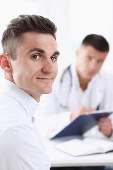 彼のオフィスで医者と満足のハンサムな笑みを浮かべて男性患者。高レベルおよび質の高い医療サービスのセラピストの相談の仕事とキャリアの物理的な健康的なライフスタイルのコンセプト
