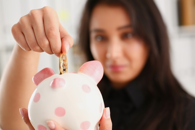 ビットコインコインを手に持った若い笑顔の中国人女性は、暗号通貨で貯金箱を貯めるピンク色の貯金箱の形にそれを押し込みます。