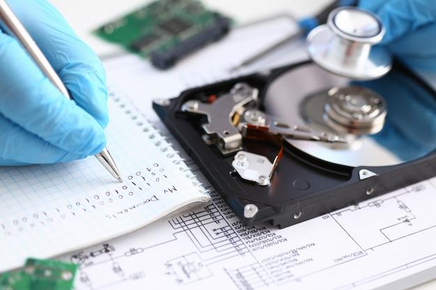 コンピューターのラップトップからのハードドライブに聴診器を手で保持している青い手袋をはめた男性の修理。故障診断を実行し、削除クローズアップ中に失われたデータを回復する緊急修復を実行します