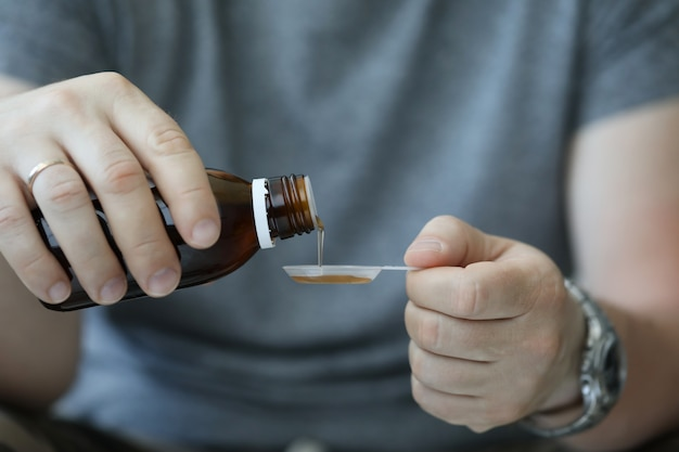 病院の男の男性の手が咳を注ぐ