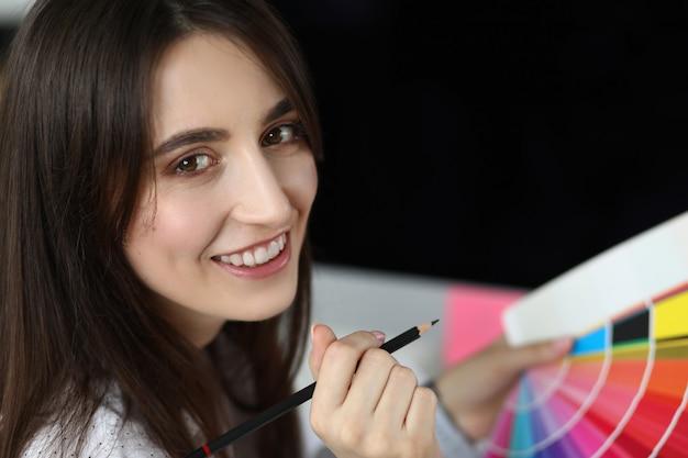 Портрет усмехаясь творческой женщины держа цветовую схему и карандаш.