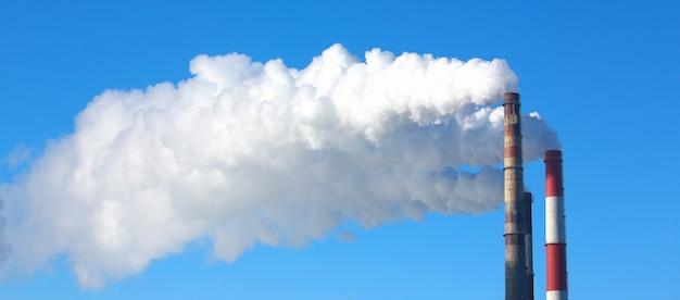 白い煙は青い空を背景にパイプから来ています。大都市エココンセプトのセントラルヒーティング人口の問題の有害な排出と大気汚染