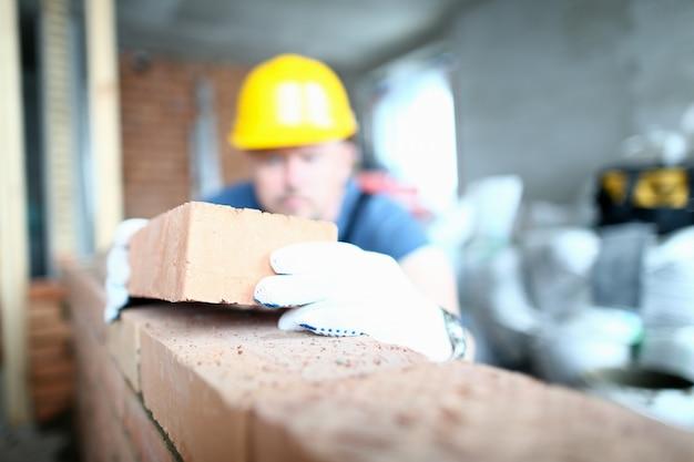Сосредоточьтесь на трудолюбивого конструктора, кладущего красный кирпич на бетонную стену со строгой точностью.