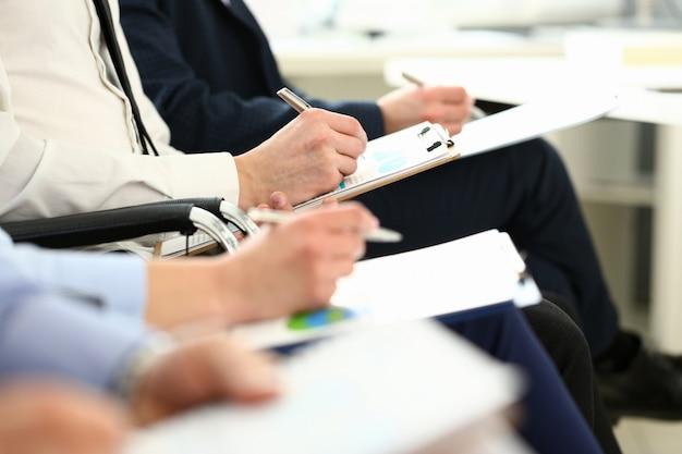 スマートワーカーの手に集中して、紙のフォルダーに何かを書き留めます。重要な企業契約について話し合うマネージャー。会社会議コンセプト