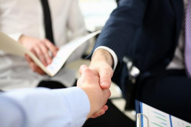 男性の握手に焦点を当てます。ビジネス文書と契約の重要なトピックを同僚と議論するトレンディなスーツの上司。会社会議コンセプト