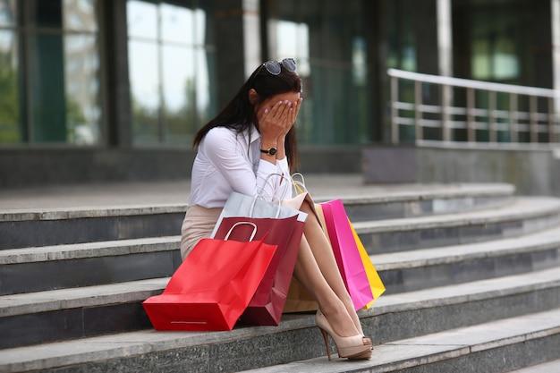 手でかわいい顔を覆っている完璧な女性の肖像画。通りの階段にパッケージで座っている美しいモデル。ファッションとショッピングのコンセプト。