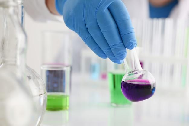 男性の化学者がガラスの試験管を手に持ってカリウムの液体溶液をあふれさせる