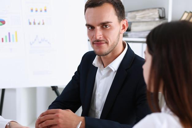 人々のグループは、オフィスのクローズアップでホワイトボードの問題を熟考します。