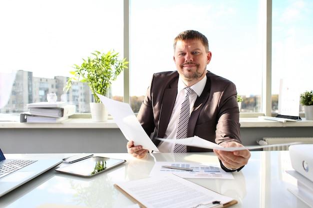 Мужчина в костюме и галстуке держит в руках документы в офисе