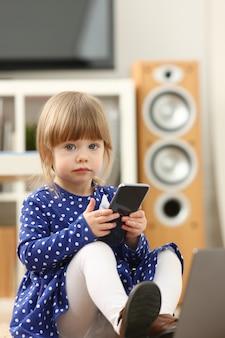 床のカーペットにかわいい女の子が携帯電話を使用します。