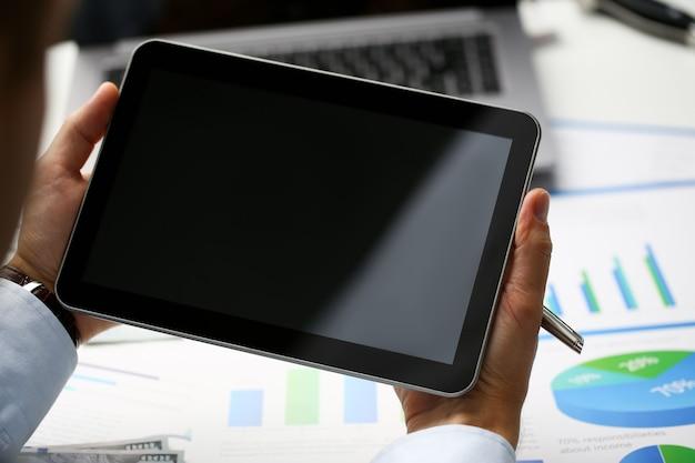 Бизнесмен держит цифровой планшет с пустым темным экраном