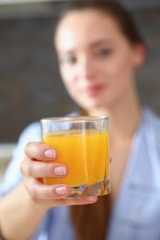 美しい女性はオレンジジュースのグラスを腕で保持します。