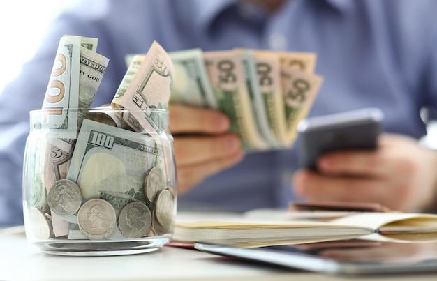 豊富な瓶いっぱいまたは米国の紙幣と実業家の腕を持つコイン